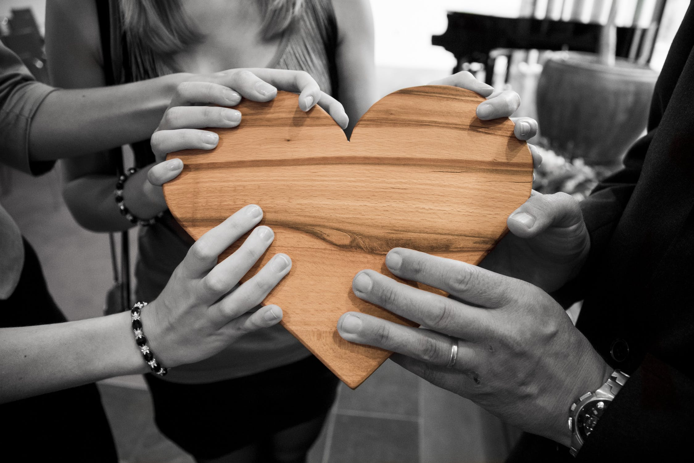 Black and white photo of hands holding a wooden heart