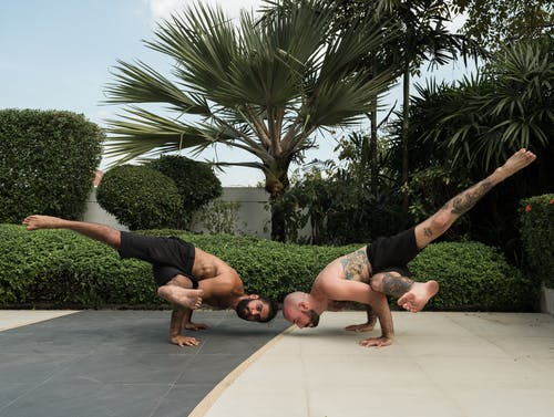 Photo of Two Men Doing Yoga