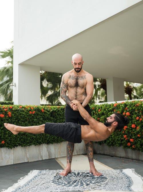 Shirtless strong sportsmen practicing acro yoga