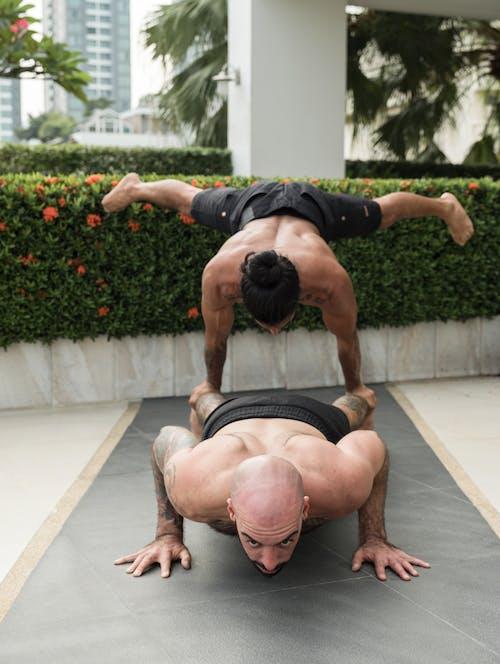 Muscular brutal sportsmen doing acro yoga exercises