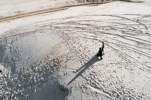 Unrecognizable persons walking on white sand