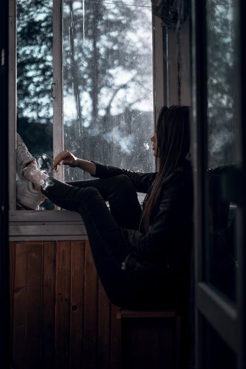Side view of unrecognizable calm lonely female teenager sitting near open window in dark room and looking away pensively