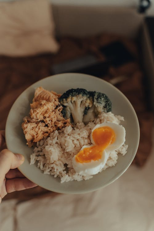 From above of crop anonymous person holding plate with homemade lunch including fried fish with broccoli and boiled egg served with rice