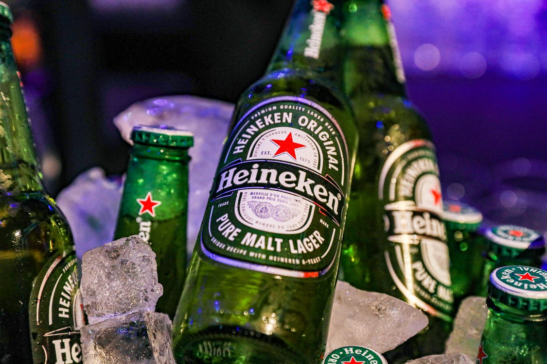 Closeup of green glass bottles of cold famous lager beer against blurred background with neon lights during party