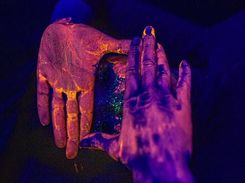 Unrecognizable female covering painted face with hands covered with colorful pigment in dark studio with neon illumination