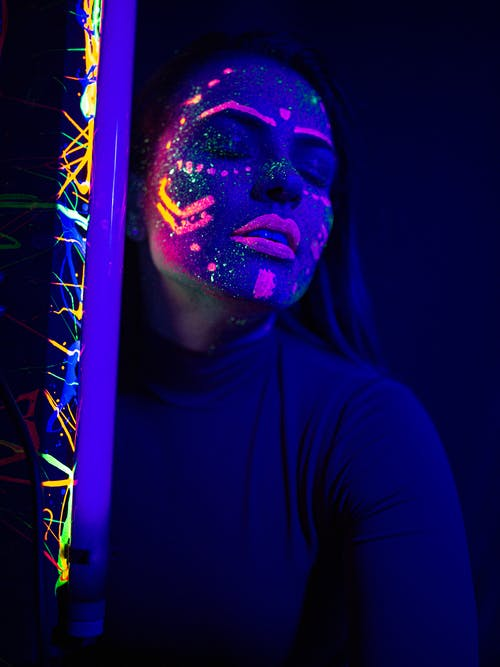 Calm woman with neon paints on face and UV lamp