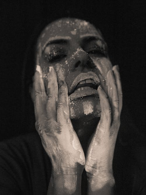 Young woman with painted face touching cheeks