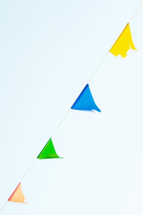 Multicolored string of pennant flags against blue sky