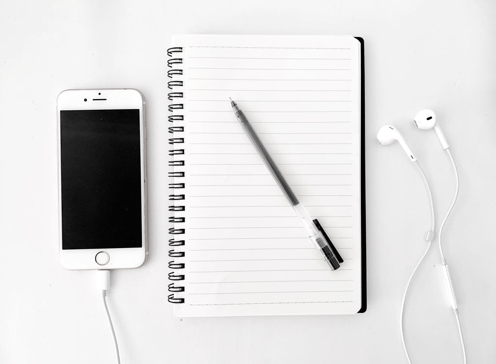 Top view arrangement of spiral notebook with blank sheets and pen placed on white desk near modern mobile phone with earphones