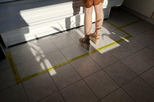 Woman in Brown Skirt and Black Flip Flops Standing on Gray Floor Tiles