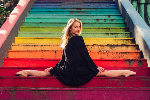Positive flexible woman performing split on multicolored street staircase