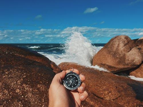 Crop traveler with compass on stony seashore
