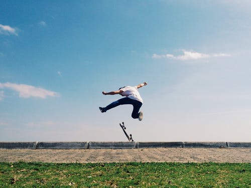 Man in White Shirt and Blue Denim Jeans Jumping on Green Grass Field Under Blue Sky