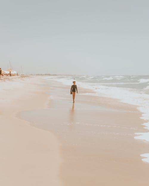 Unrecognizable child walking on wet sandy seashore