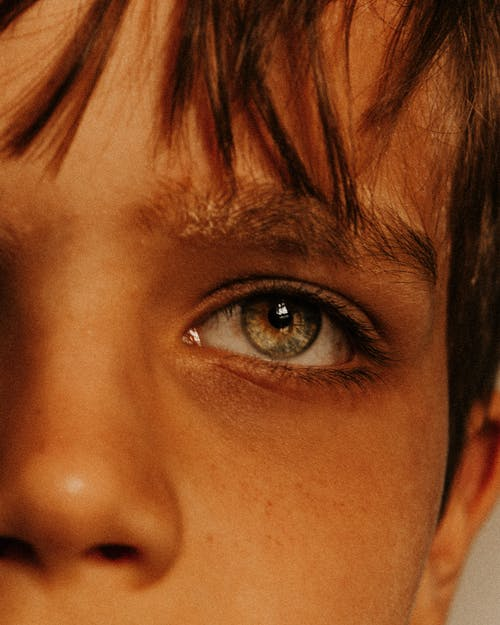 Closeup crop face of calm thoughtful boy with fathomless gray green eyes and bangs