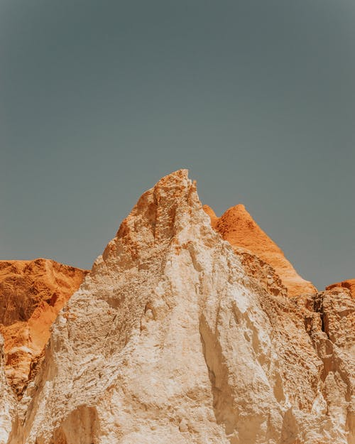 Rough rocky formation against blue sky