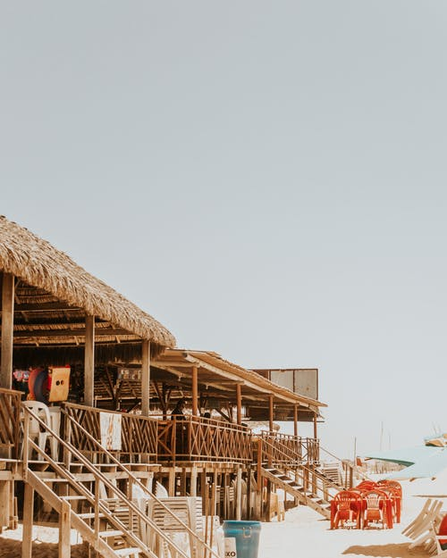Wooden thatched beach constructions in sunlight