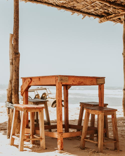Comfortable wooden table with stools placed under thatch roof in beach cafe against calm sea during hot summer day