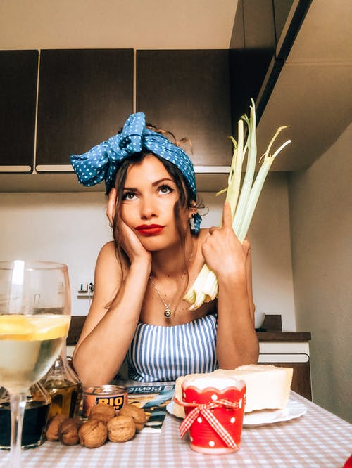 Bored trendy woman with celery sitting at table in kitchen
