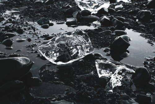 Pieces of ice on rocky ground with water