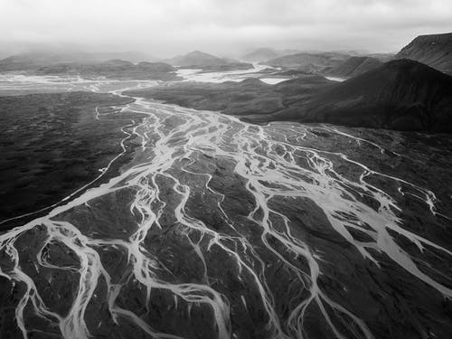 Distance black and white scenery of rough mountainous terrain with breathtaking pattern of glacier frozen rivers under cloudy sky