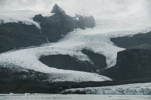 Severe Nordic landscape of snowy mountain slopes covered with ice located near cold sea with black and white effect