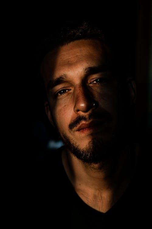 Content bearded man in dark room