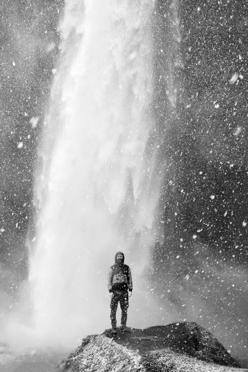 Man standing against strong waterfall in winter