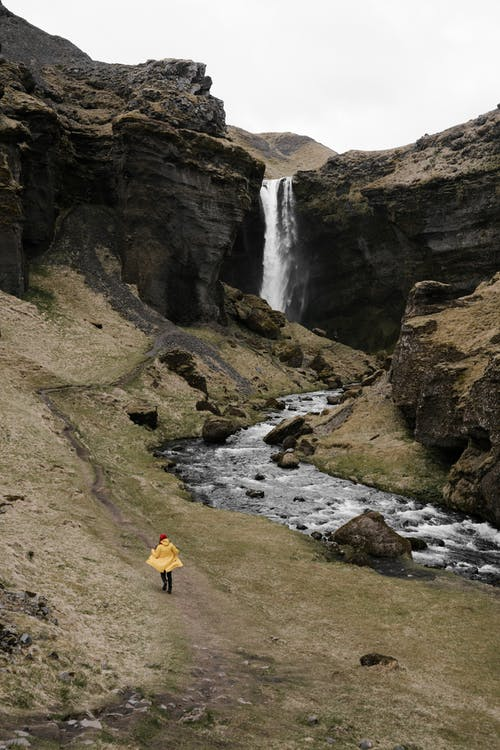 Unrecognizable traveler walking on mountain slope near waterfall
