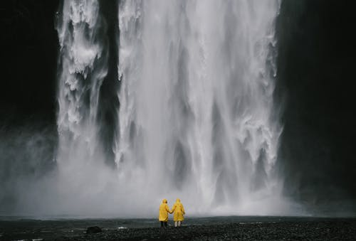 Anonymous travelers holding hands against spectacular waterfall