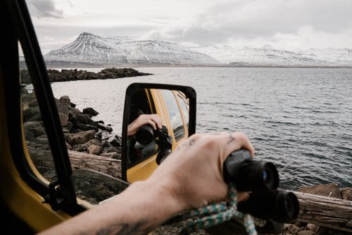 Unrecognizable traveler with binoculars admiring nature from car