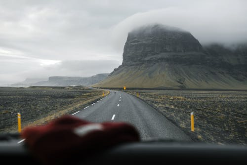 Through glass of empty asphalt road going through valley with mountain slopes against foggy sky