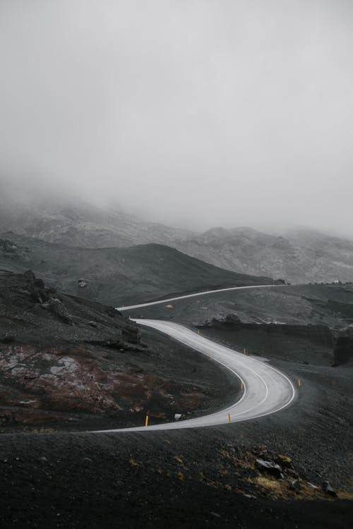 Scenery of road among mountains hiding in fog