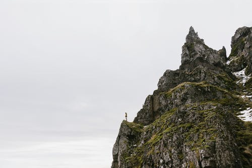 From below of unrecognizable hiker standing alone on edge of rocky cliff against cloudy sky