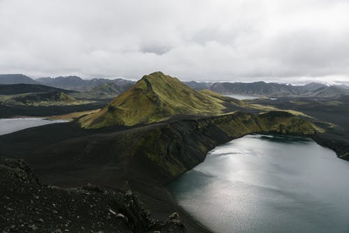 Drone view of majestic calm lake surrounded by volcanic mountain ranges in Iceland