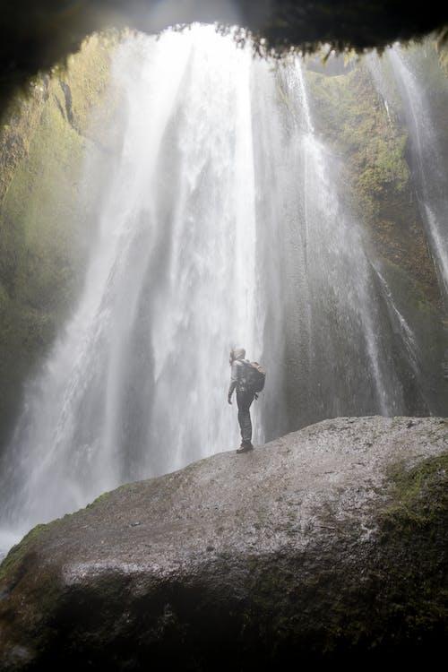 Anonymous person enjoying waterfall in canyon