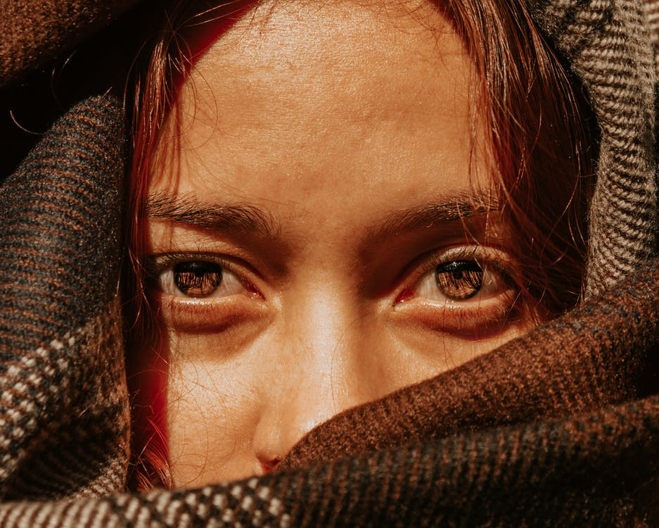 Crop unemotional female with brown eyes covering pretty face with warm brown scarf and looking at camera
