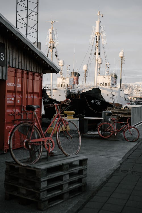 Bicycle on shabby wooden pallet in harbor