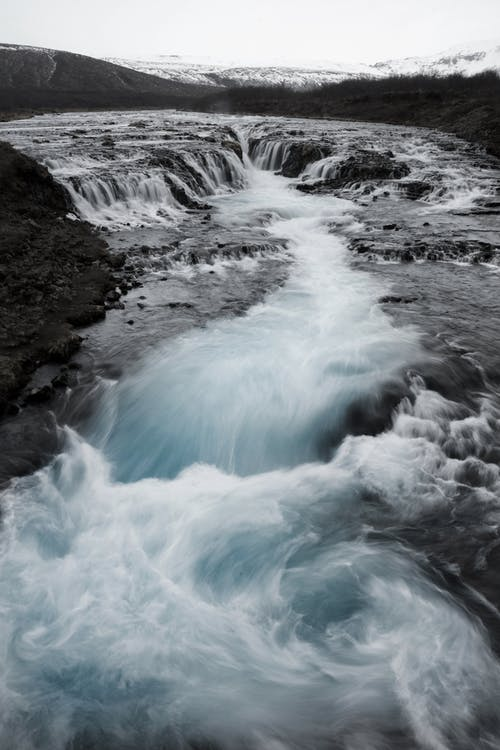 From above of rough rocky volcanic terrain and swirling Bruarfoss waterfall with turquoise water