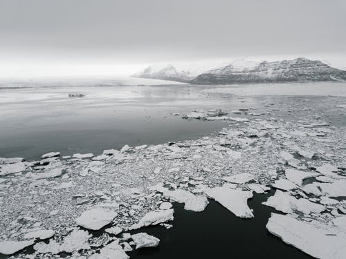 Antarctic landscape with broken ice on water and frozen mounts