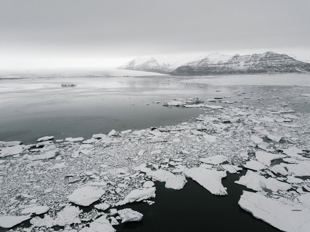 Antarctic landscape with broken ice on water and frozen mounts