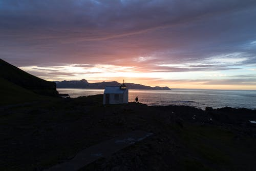 Small house with unrecognizable person on seashore at sunset