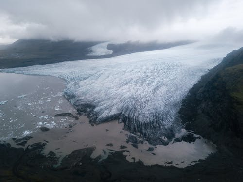 Majestic glacier tongue reaching seashore under gloomy misty sky
