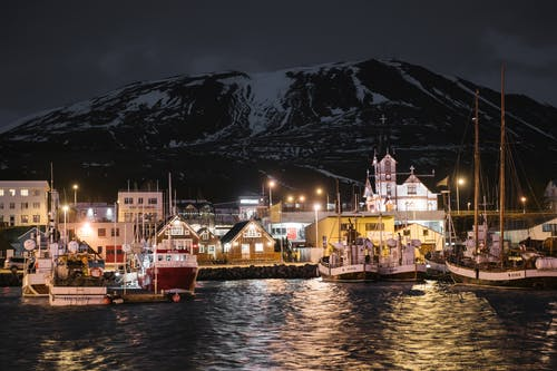 Seafront of brightly lit Husavik harbor late at night in Iceland with sailboats at quayside and dark snow covered mountain in background