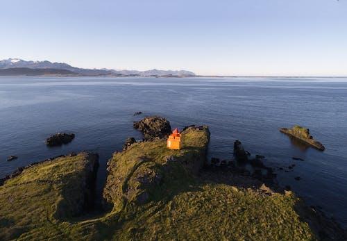 Little lighthouse on rocky seashore on sunny day