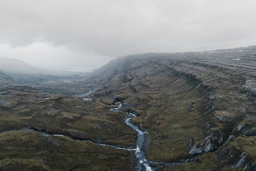 Mountainous terrain with small wild river in foggy day