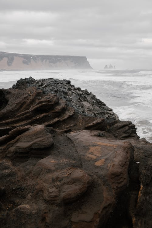 Rough northern stony coast of misty rippling sea with foamy waves under cloudy sky