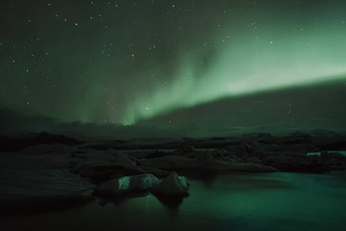 Dark stony terrain under starry night sky with amazing Aurora Borealis glowing with vibrant green color