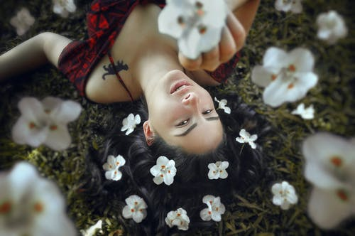 A Woman Lying on the Grass Surrounded with Flowers