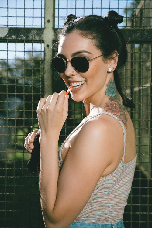 Tattooed woman in sunglasses standing against metal fence
